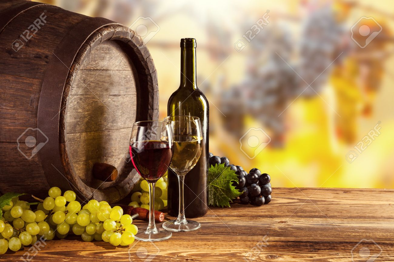 46446668-red-and-white-wine-bottle-and-glass-on-wooden-keg-grapes-of-wine-on-background.jpg